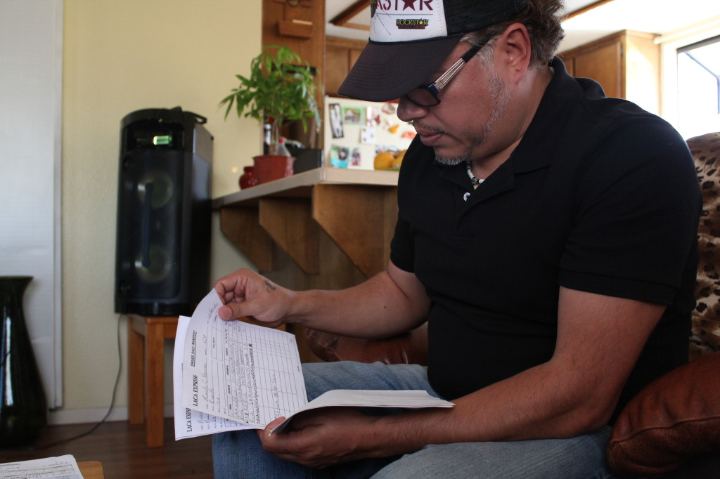 Ricardo Ceja reviews his paystubs at his Lawndale apartment. | Daina Beth Solomon